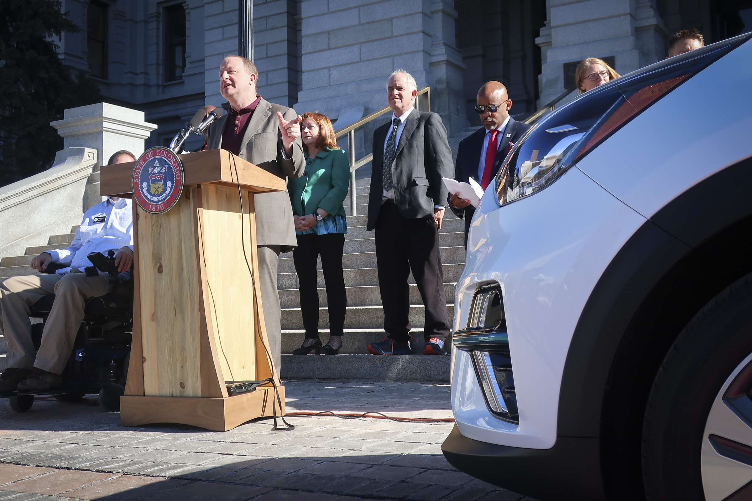 Gov. Jared Polis speaks at a press conference where ride-hailing company Lyft announced it would add 200 electric vehicles to its fleet in Denver on Thursday, Nov. 14, 2019.