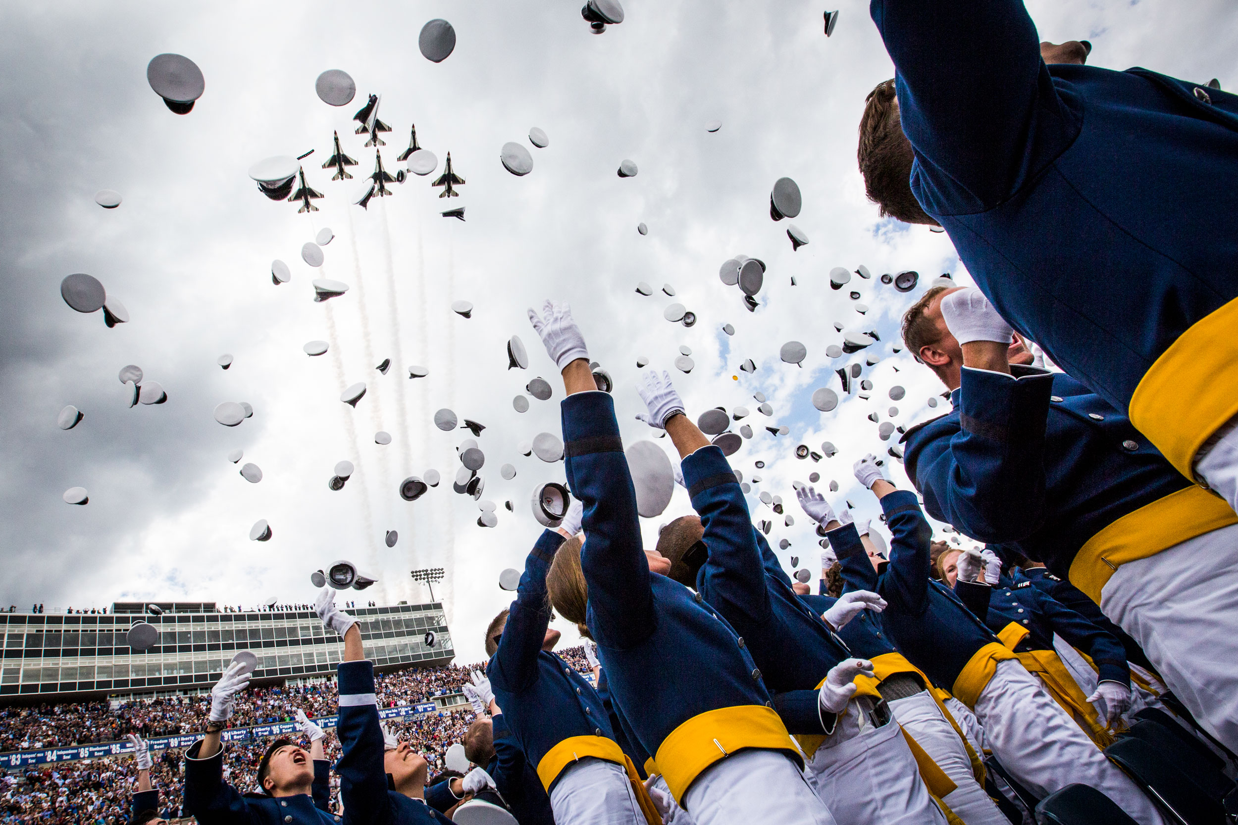Air Force Academy cadets throw their hats into the air during their May gtraduation ceremony, at the exact moment ther Air Force Thunderbirds precision flying team flies overhead. President Donald Trump delivered the commencement address this year.