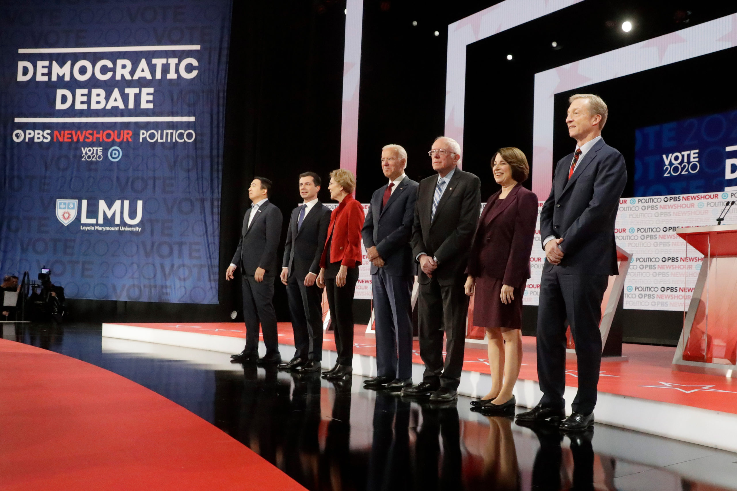 Democratic presidential candidates from left, entrepreneur Andrew Yang, South Bend Mayor Pete Buttigieg, Sen. Elizabeth Warren, D-Mass., former Vice President Joe Biden, Sen. Bernie Sanders, I-Vt., Sen. Amy Klobuchar, D-Minn., and businessman Tom Steyer stand on stage before a Democratic presidential primary debate Thursday, Dec. 19, 2019, in Los Angeles, Calif.