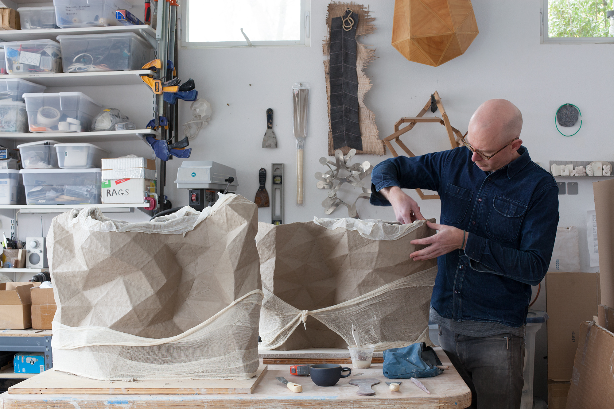 Artist Del Harrow working in his studio on hand-built clay vessels which borrow surface textures from digital models.