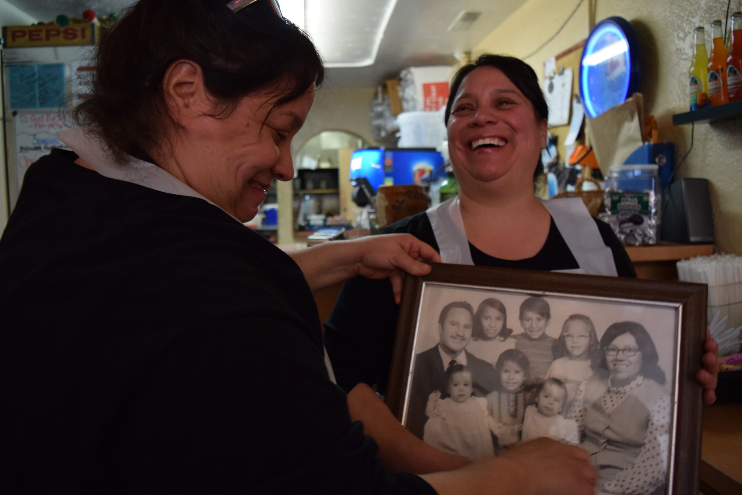 Jana Mitchell, left, points out who is who in the family portrait to her sister, Judy Allen. They took over management of El Taco Rey in Colorado Springs from their parents.