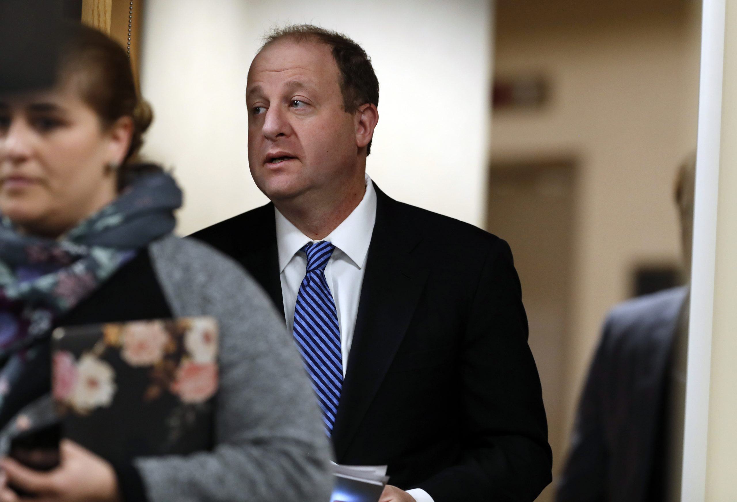 Colorado Governor Jared Polis enters a news conference as a statewide stay-at-home order remains in effect in an effort to reduce the spread of COVID-19, Wednesday, April 1, 2020, in Centennial, Colo.