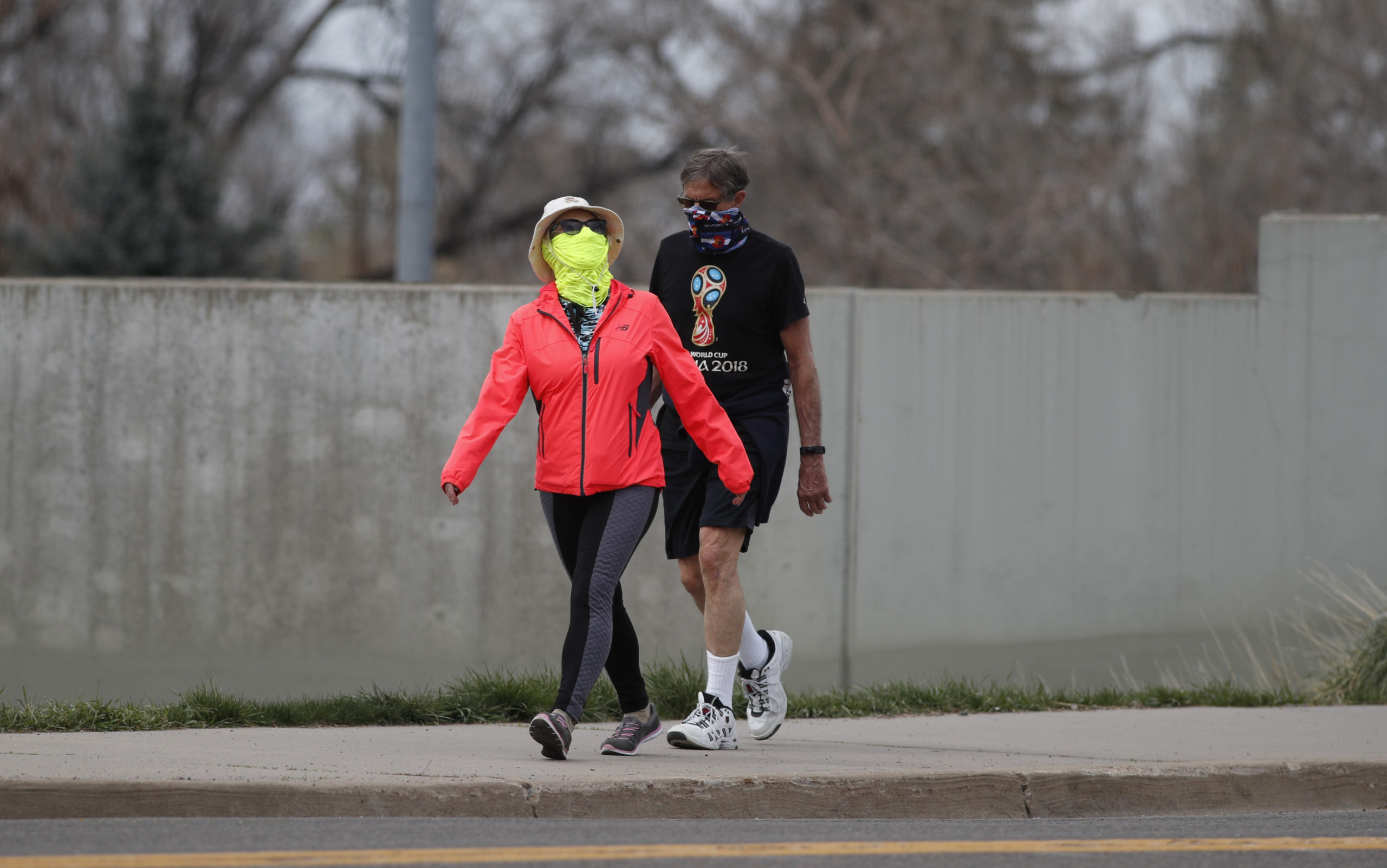 Pedestrians wear masks to comply with a request by Colorado Gov. Jared Polis while they walk along South St. Paul Street as a statewide stay-at-home order remains in effect in an effort to reduce the spread of the new coronavirus, Sunday, April 5, 2020, in Denver.