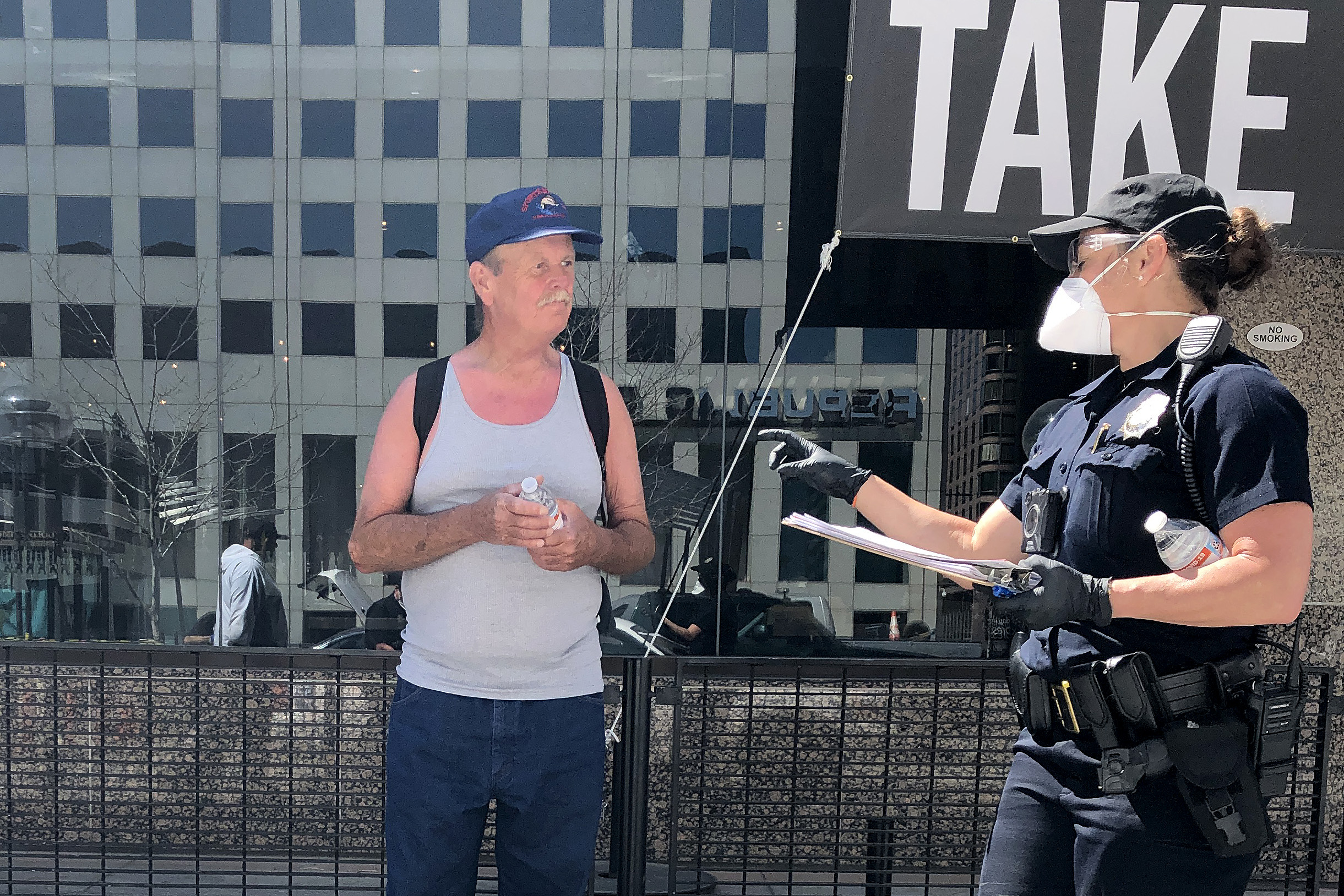 Denver Officer Teresa Gillian, in face mask, handing out water on April 7, 2020.
