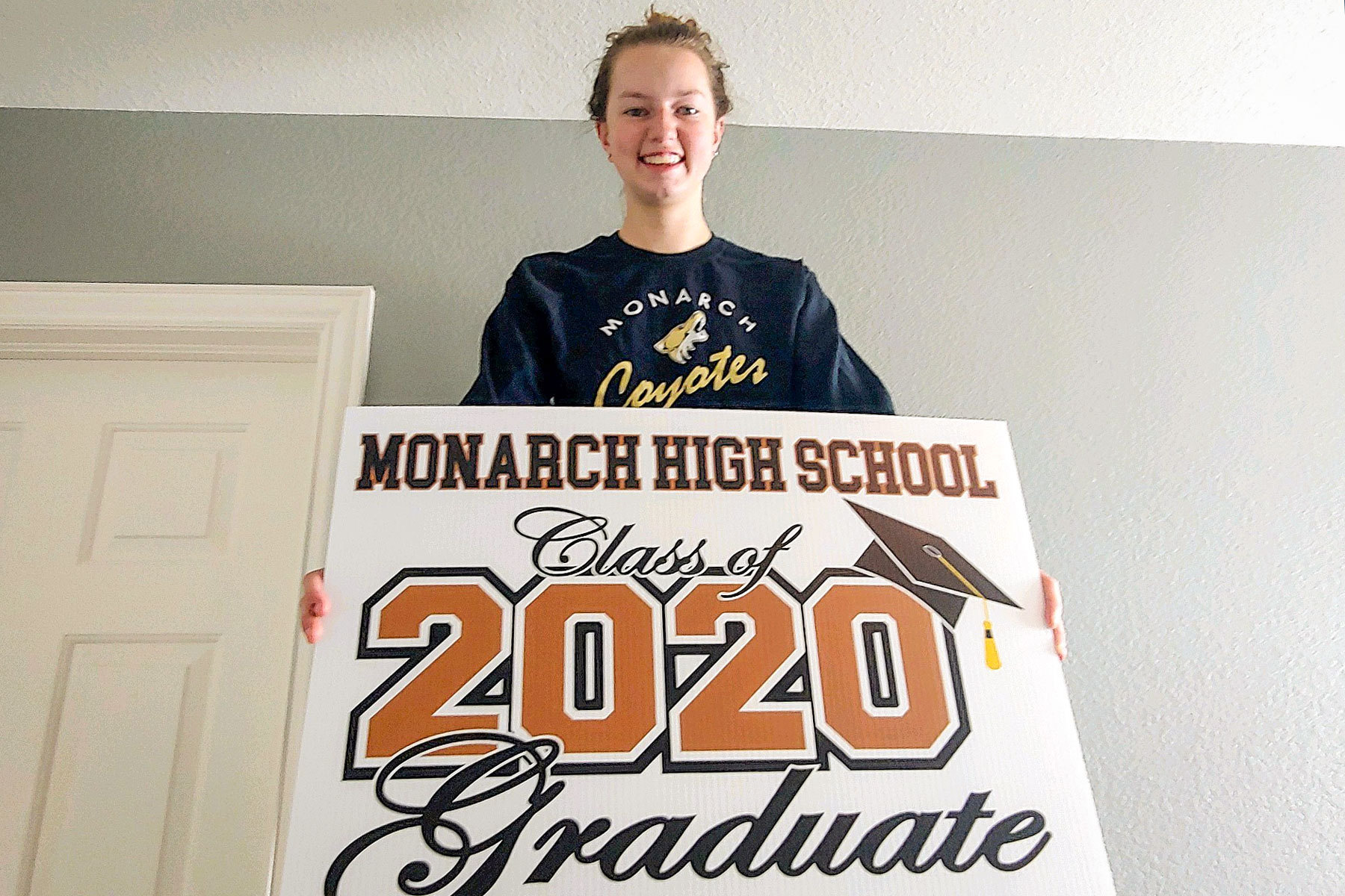 Julia Mainland holds up a lawn sign the Monarch High Booster Club gave to seniors.