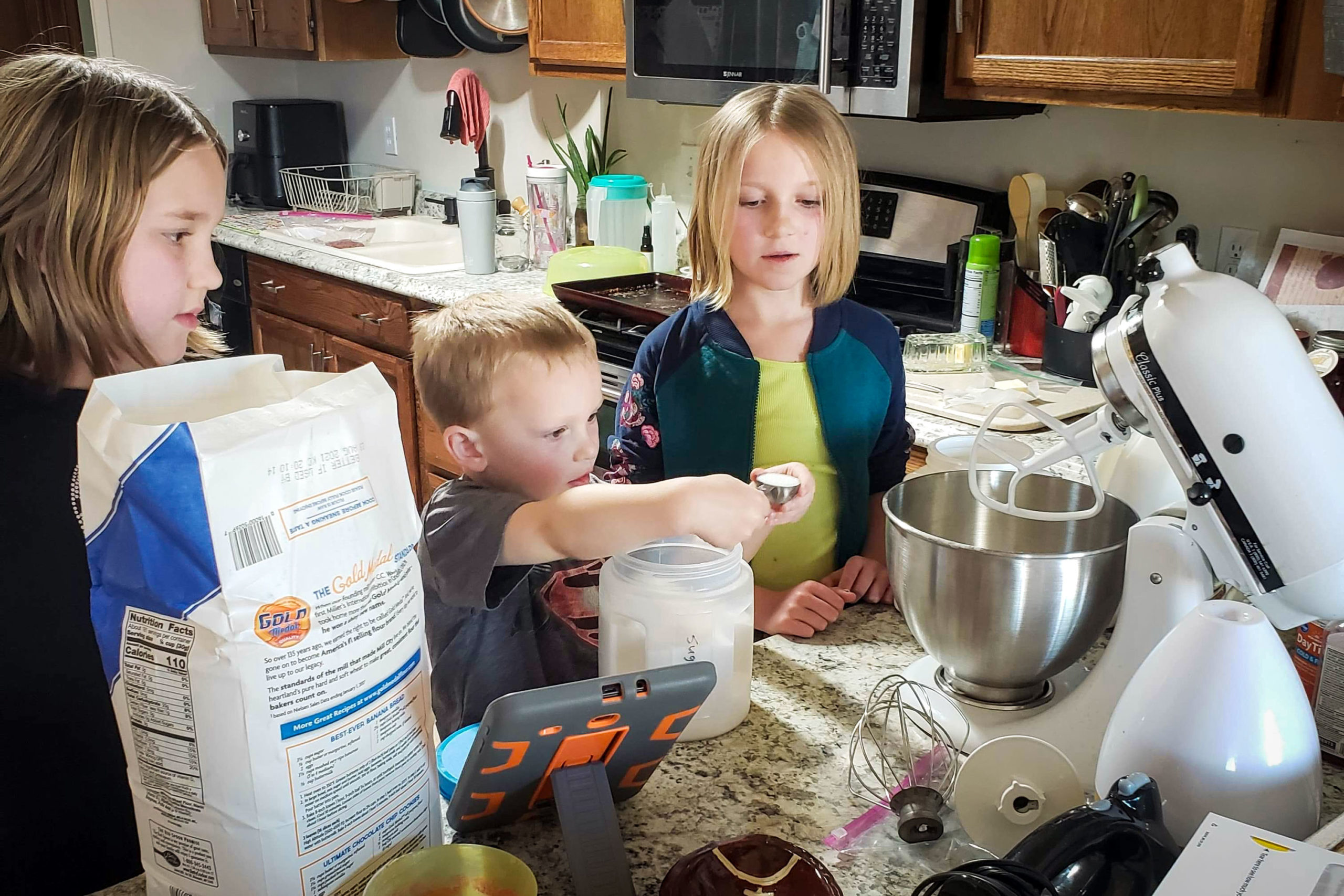 Since the pandemic began, Grand Junction stay-at-home mom Julie Baker has been inspired to bake more than she has in years, and has even borrowed a mixer from a friend to help the family make treats. She and her four kids recently made sour milk biscuits. Above, from left, are Katy, 9; Daniel, 3; and Lizzie, 8.