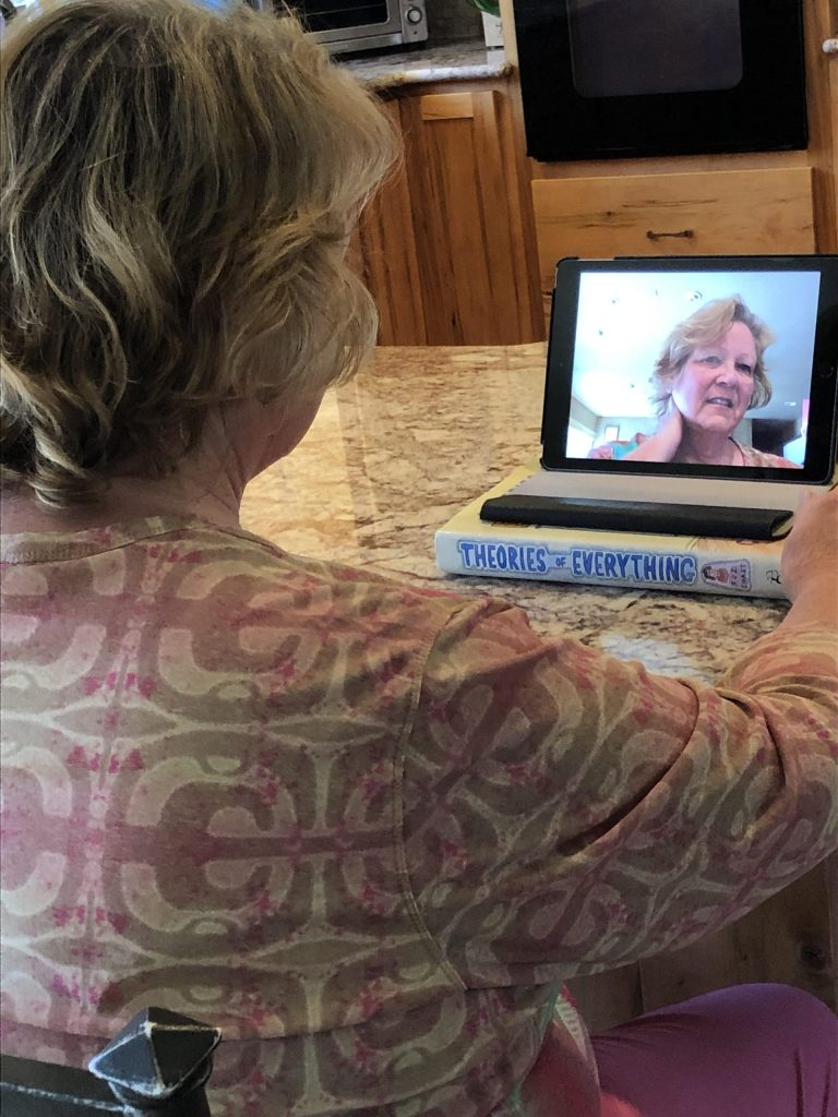 A picture of Cynthia getting ready in her Zoom call. Her refection can be seen on the laptop screen placed on her table.
