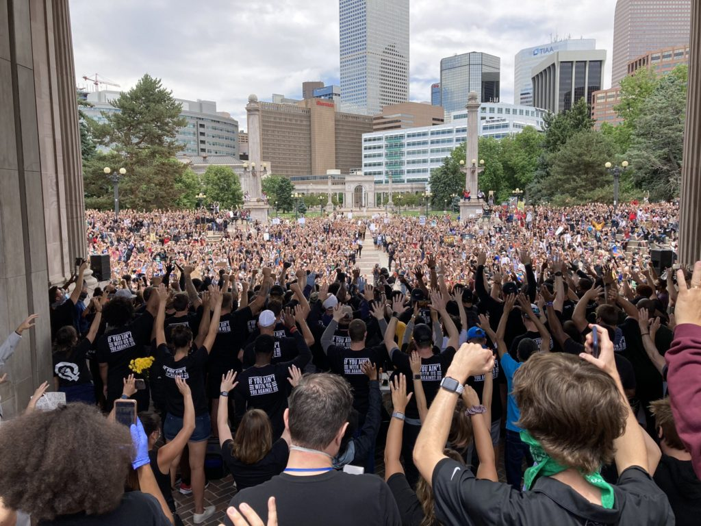 Protesters stand in unison at Civic Center Park on June 6, 2020, to fight racism and police brutality.