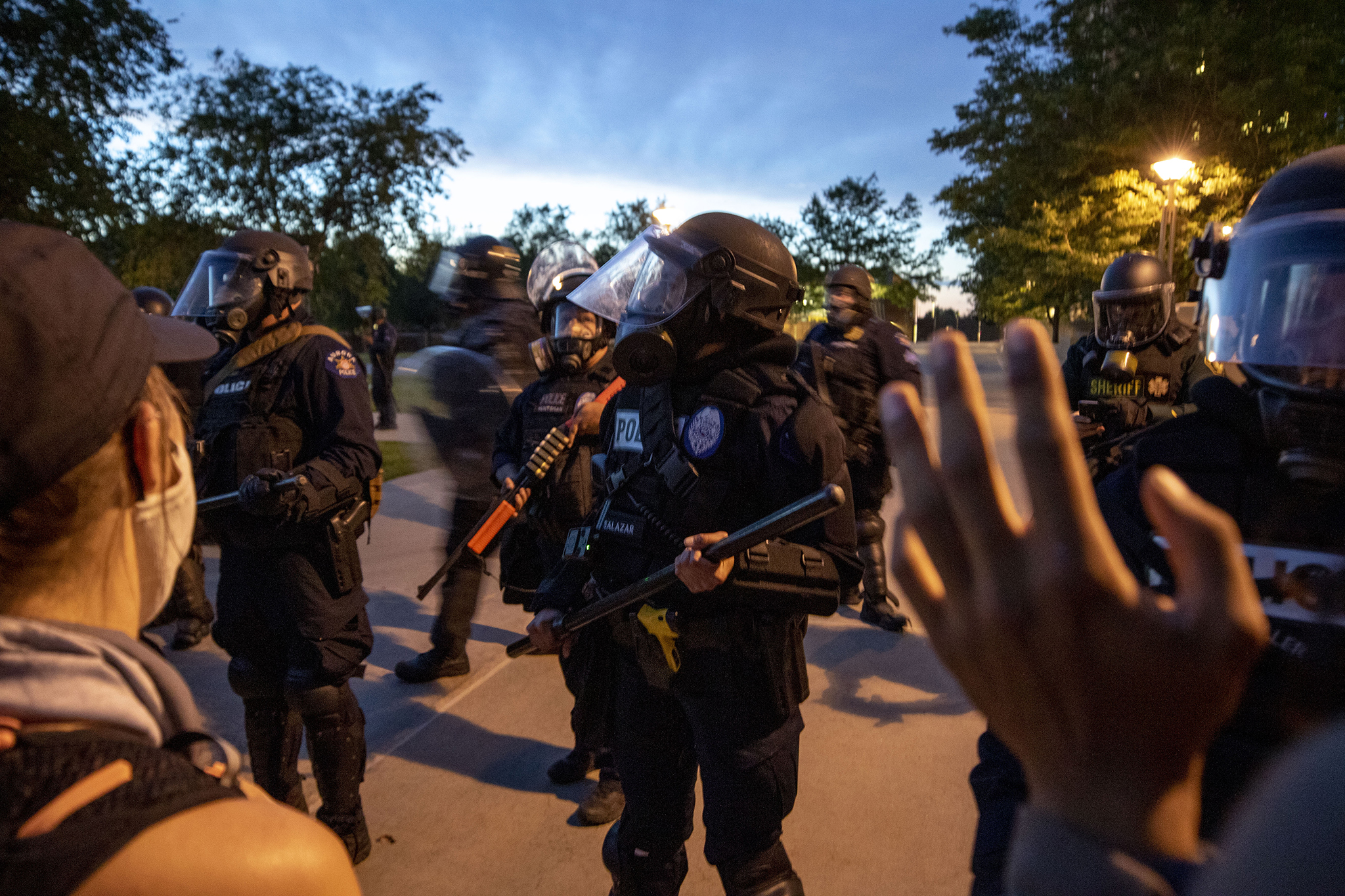 Aurora Police officers push protesters and musicians away from the municipal complex's lawn after a series of rallies and protests demanding justice for Elijah McClain. June 27, 2020.