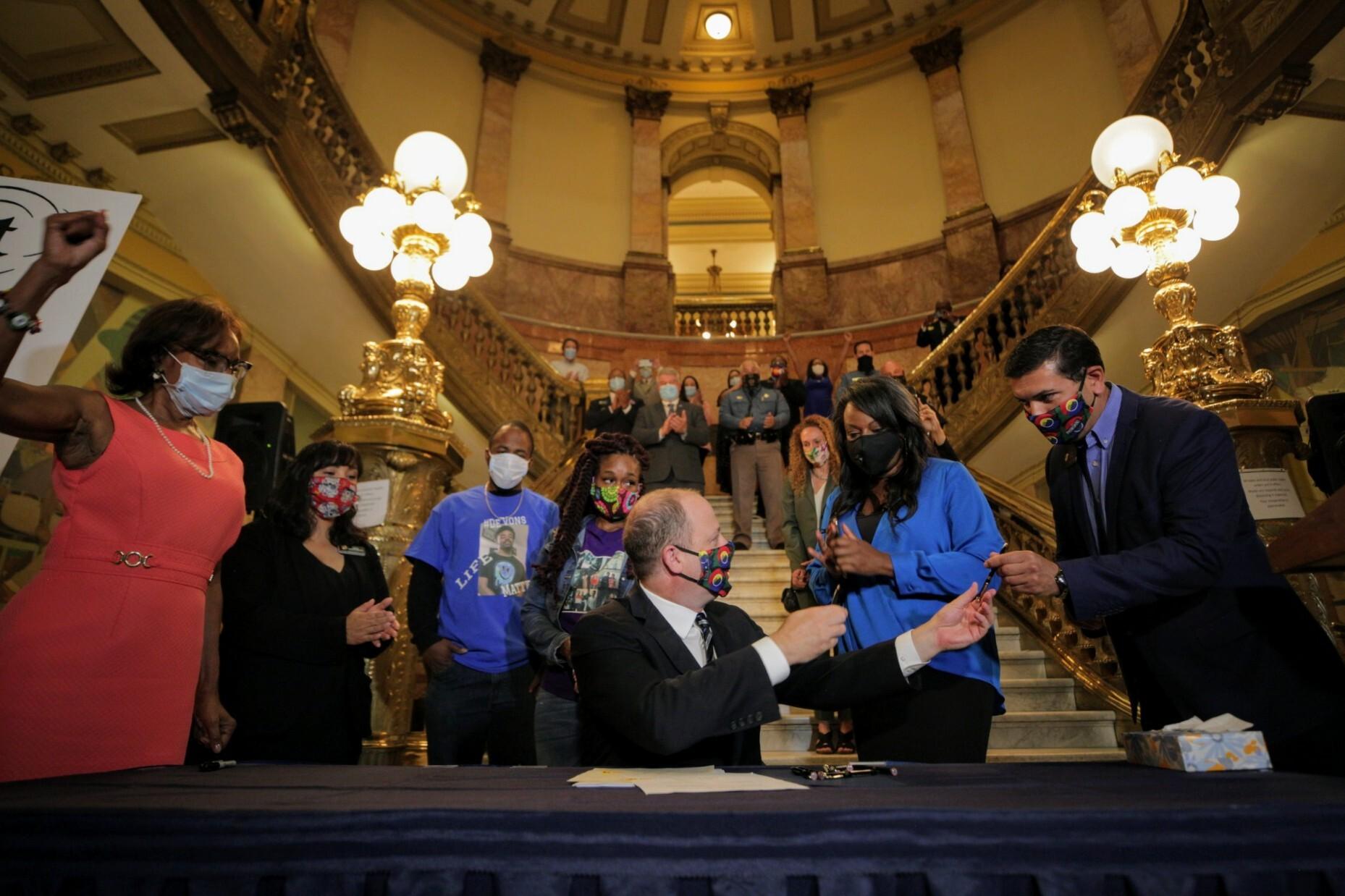 Gov. Jared Polis hands ceremonial pens to bill sponsors Rep. Leslie Herod, D-Denver and Senate President Leroy Garcia, D-Pueblo after signing law enforcement reform legislation at the State Capitol Friday