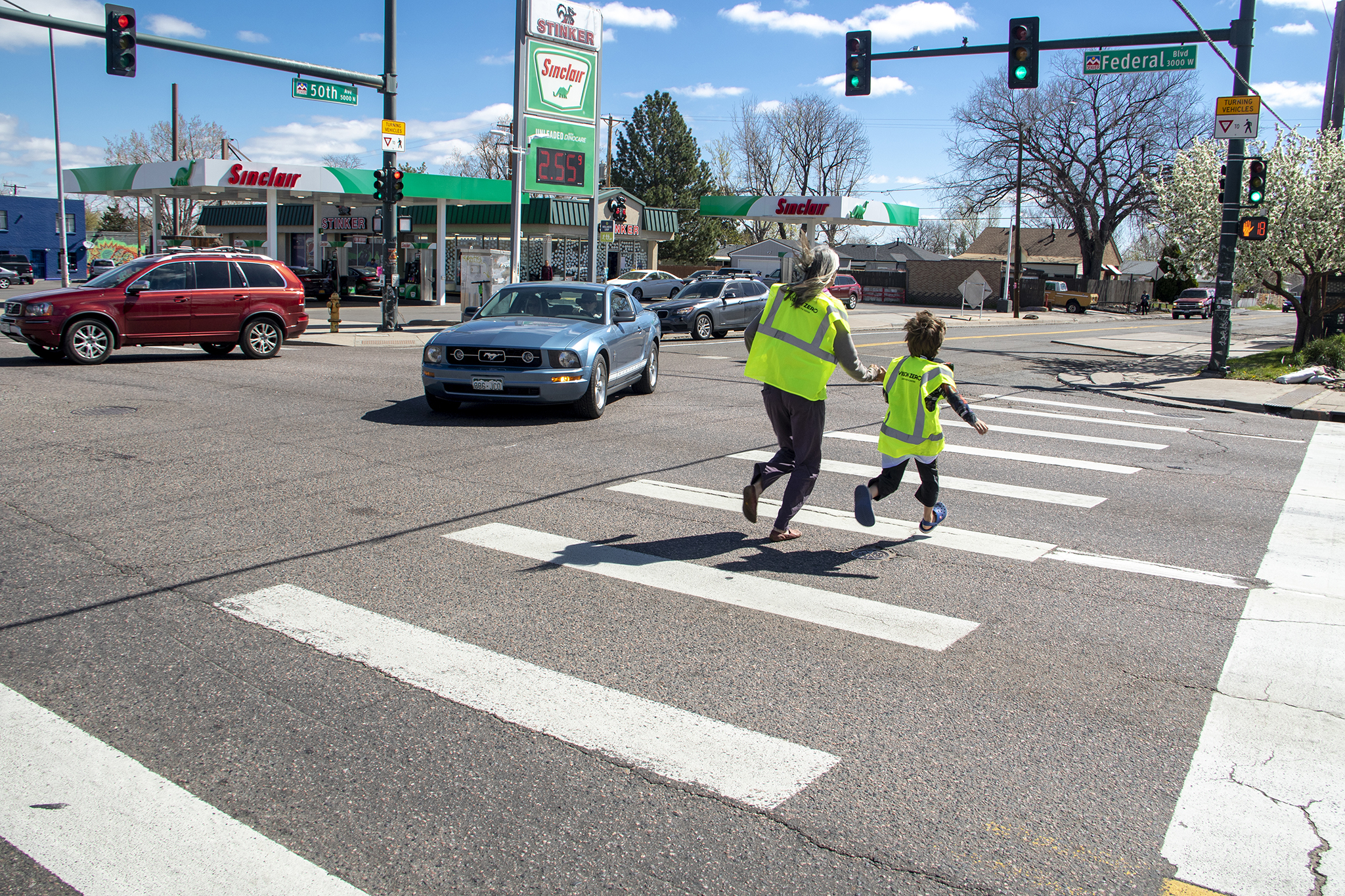 Lindsey Rosendahal and her son, Anders, runs across Federal Boulevard during a traffic slowing demo put on by Vision Zero and WalkDenver in Denver's Regis neighborhood, April 27, 2019.