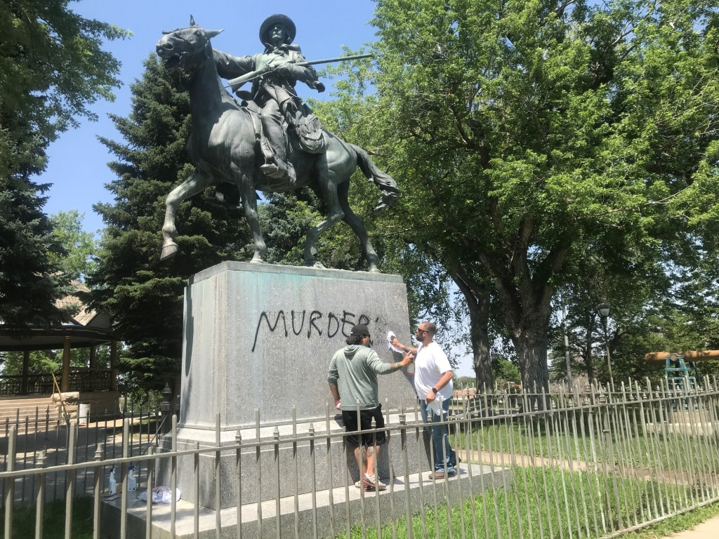 "Jay Gonzales (left) and Ty Winter clean the word ""murderer"" off the base of a Kit Carson statue in Trinidad, Colo."