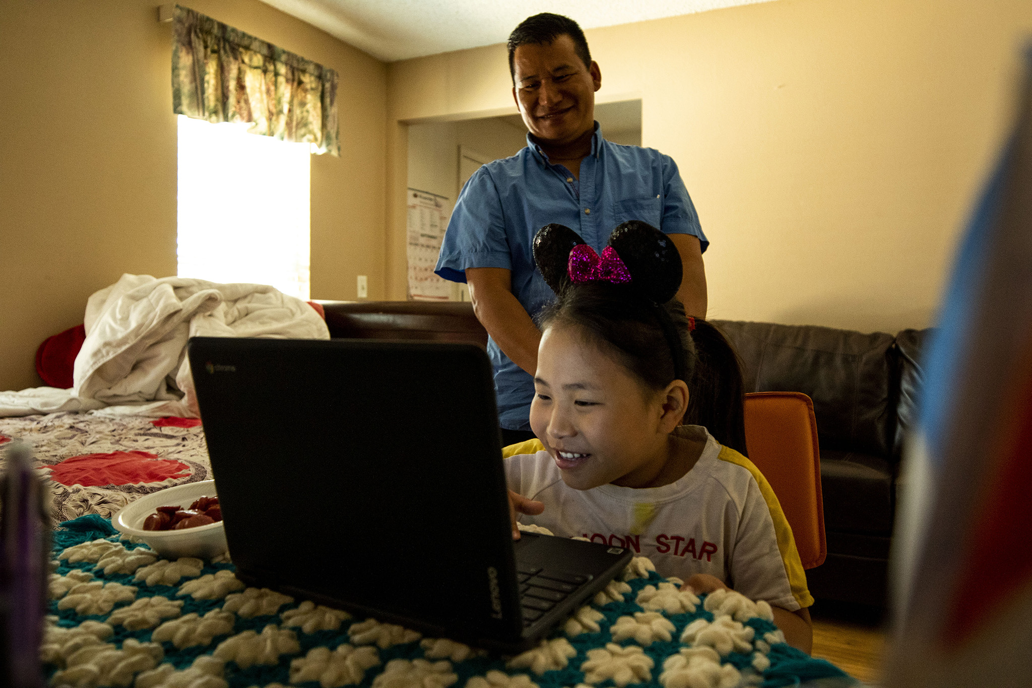 Lagan Chamling Rai watches as his daughter, Puja, works through her third day of first grade, provided virtually from Aurora Public Schools. Aug. 20, 2020.