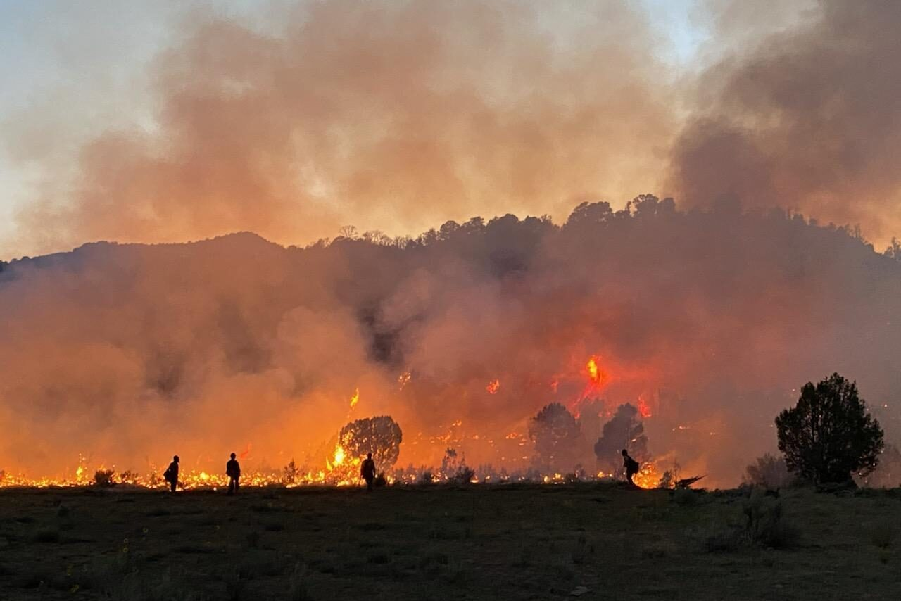 Firefighters are silhouetted by flames as they work to contain the Pine Gulch Fire north of Grand Junction, August 6, 2020.