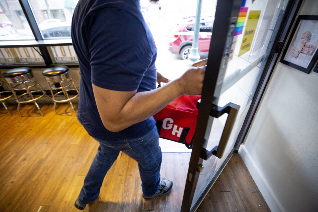 Julian Rai gingerly opens the door after grabbing a Grubhub order at Ice Cream Riot in Capitol Hill. March 13, 2020.