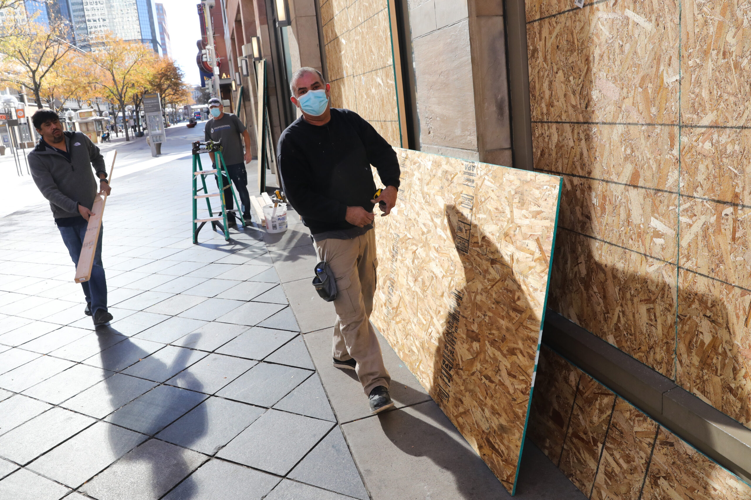 A work crew wraps the H&M store in plywood on Denver's 16th Street Mall on Monday. Many other downtown businesses are doing the same.