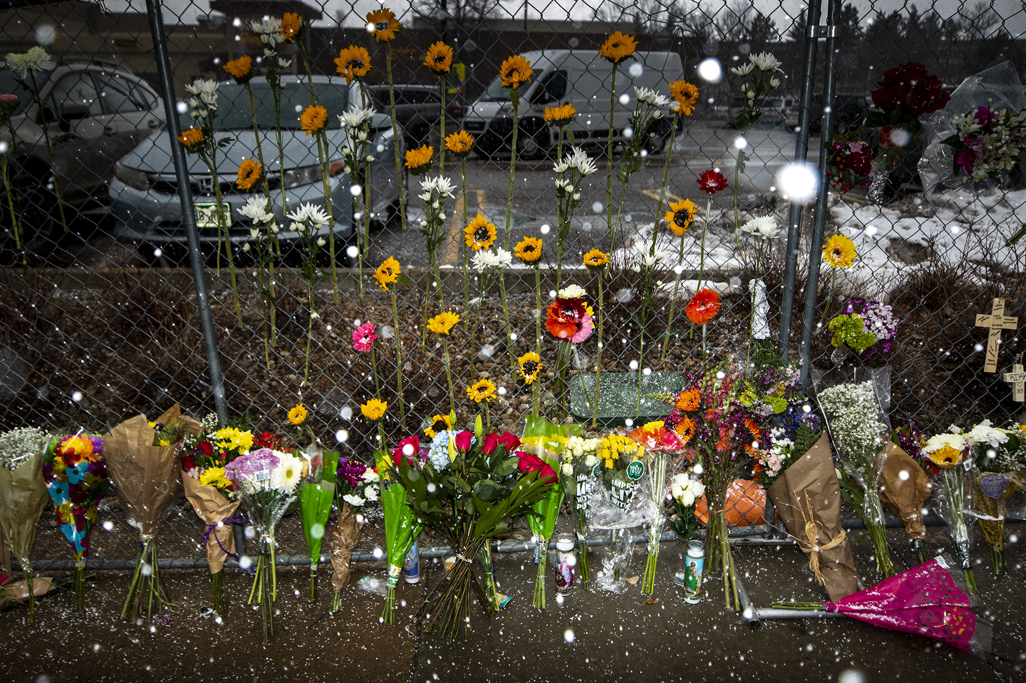 Snow falls on the makeshift memorial around the perimeter of the Table Mesa King Soopers parking lot continues to grow, Tuesday, March 23, 2021.