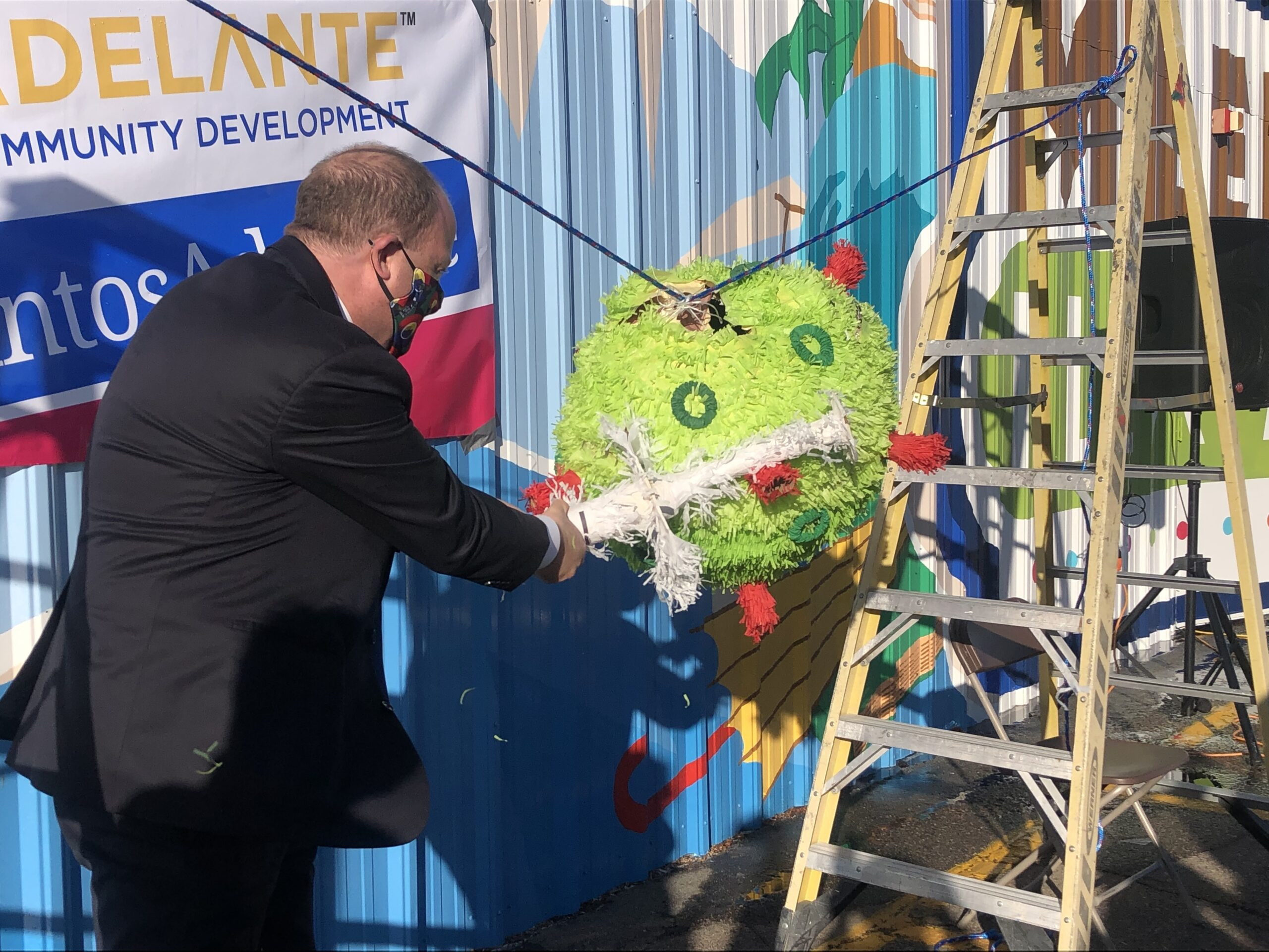 Gov. Jared Polis takes a swing at a pinata representing the COVID-19 virus, during a visit to the Adelante Community Development Clinic at Mile High Flea Market in Henderson, February 26, 2021.