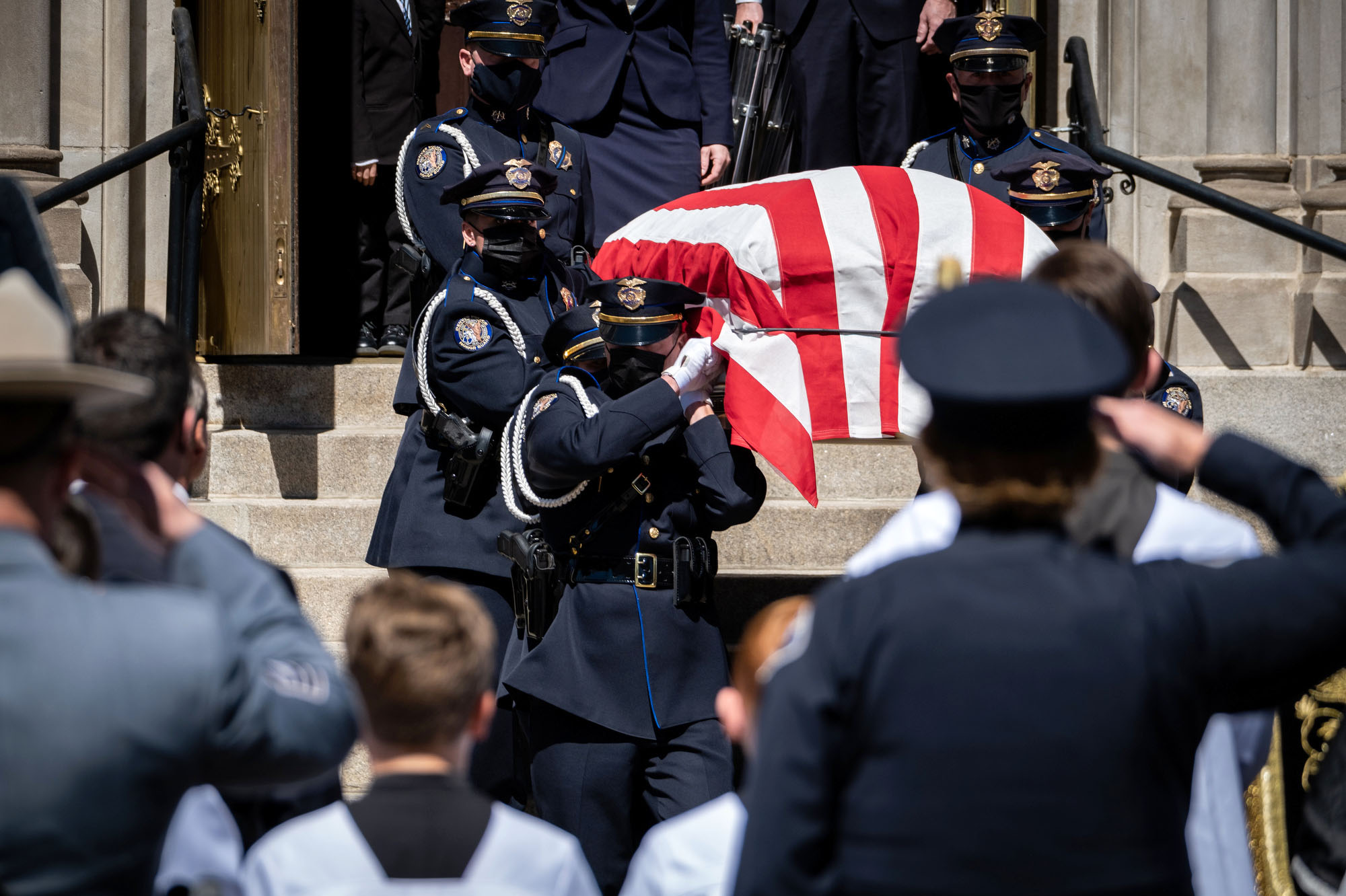 Denver Police Honor Guard members carry the casket of Boulder Police Officer Eric Talley, 51, who was killed in last week's King Soopers shooting in Boulder, down the steps of the Cathedral Basilica of the Immaculate Conception in Denver, Colorado on Monday, March 29, 2021.
