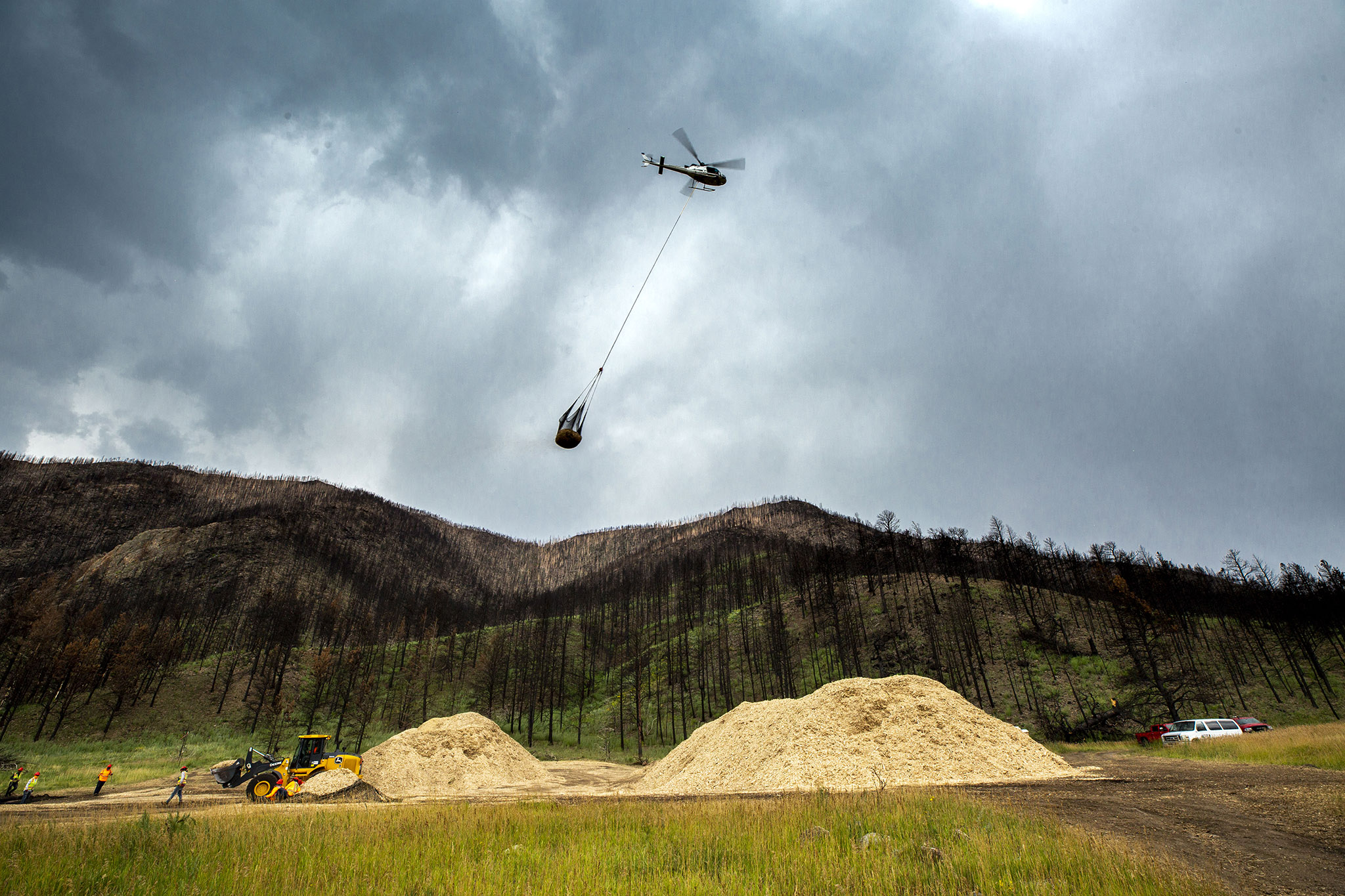 A helicopter picks up mulch to spread in Poudre Canyon, about 50 miles west of Fort Collins, to try to stem silt runoff during large rains. Aug. 8, 2021.