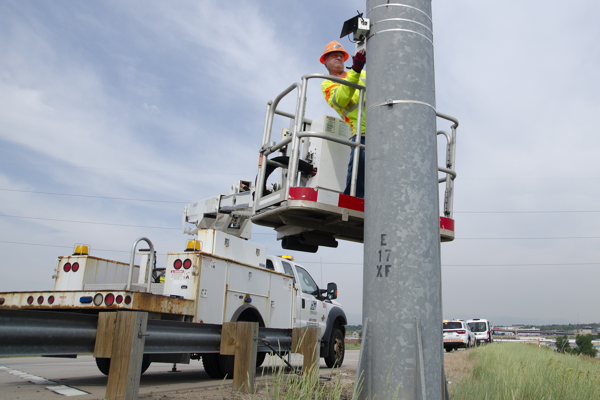 The installation of an air quality monitor on a post off the shoulder of Interstate 270 in Commerce City, Colo. on June 23, 2021.