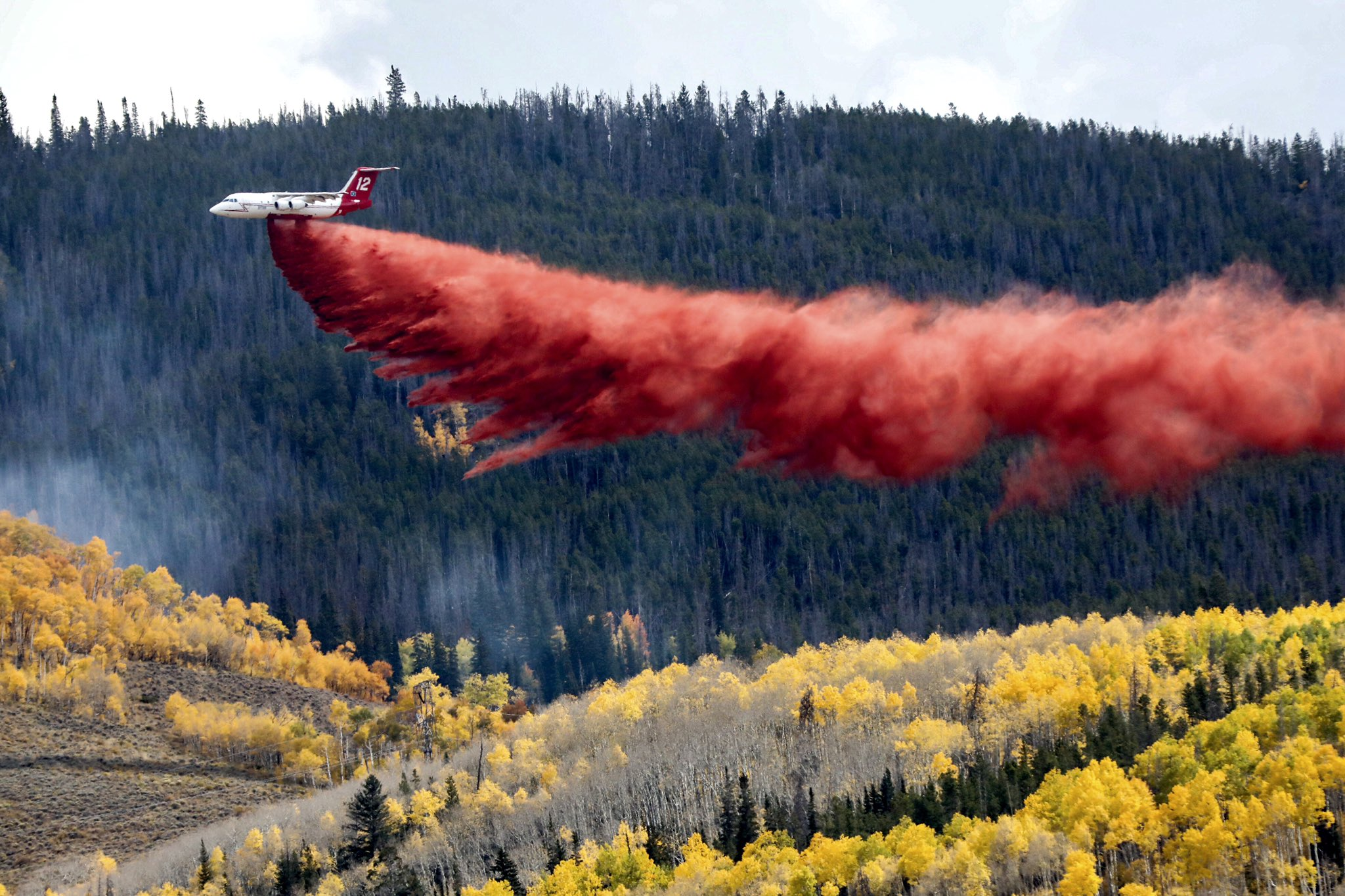 A firefighting tanker makes a slurry drop over fall aspens above Silverthorne as the Ptarmigan Fire continues to burn on Tuesday, Sept. 28, 2021.