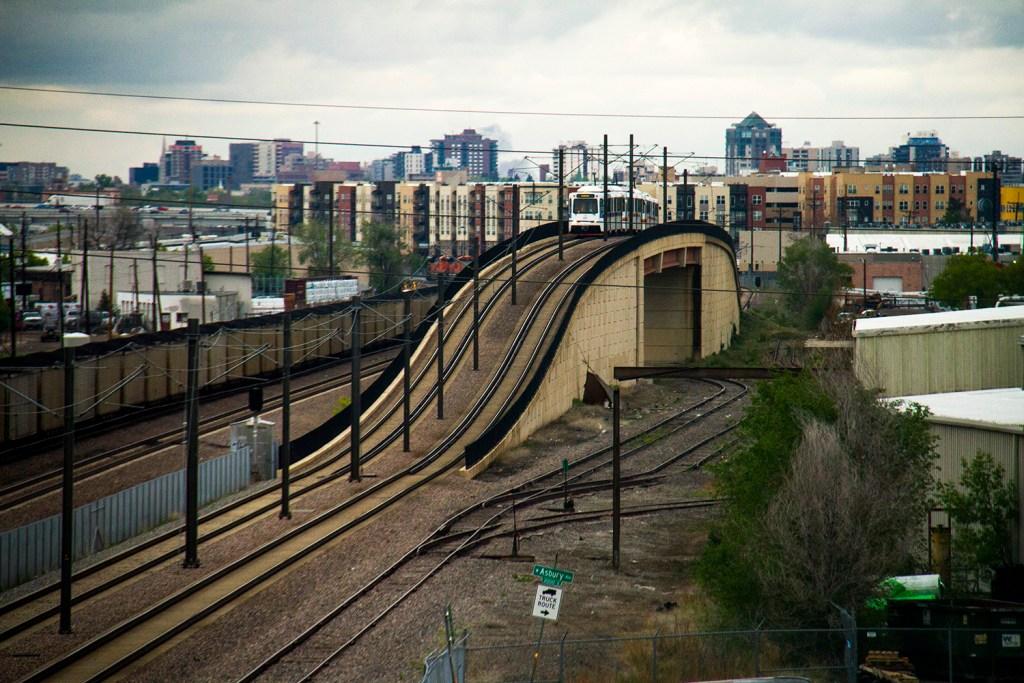 An RTD train crests over a bridge near Evans Avenue. (Kevin J. Beaty/Denverite)  light rail; train; transportation; bars; food; dining; drinks; denver; denverite; colorado; kevinjbeaty