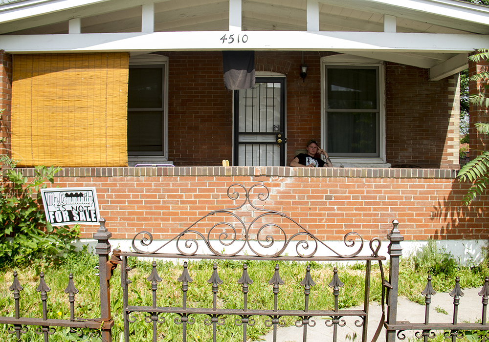 """Nathan Stickel sits on his porch in Globeville with a sign planted in his yard reading """"My community is not for sale."""" (Kevin J. Beaty/Denverite)  globeville; denver; denverite; kevinjbeaty; colorado; gentrification;"""