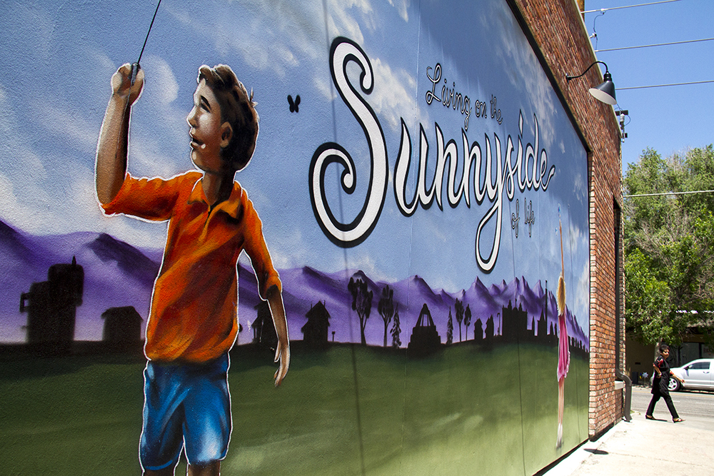 """Living on the Sunnyside,"" painted on the side of Lombards On The Avenue, a barber shop on 44th Avenue in Sunnyside. (Kevin J. Beaty/Denverite)"