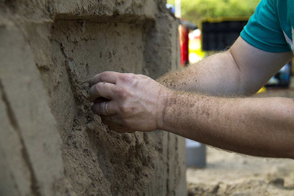 Kevin Schluckebier chisels away at the featured sculpture at Arvada's Sand in the City festival on June 25, 2016. (Kevin J. Beaty/Denverite)  sand in the city; sand castle; summer; festival; arvada; denver; kevinjbeaty; denverite; colorado;