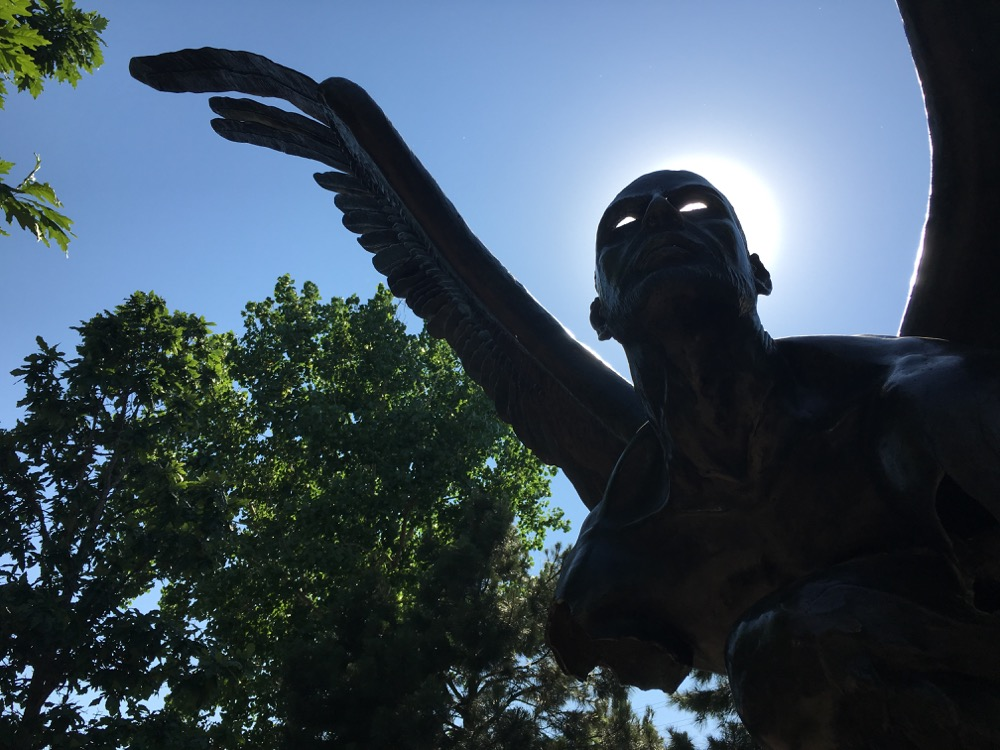 The sun shines through the hollowed-out skull of a bronze sculpture by Jorge Marín in Commons Park.