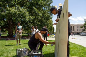 """Artist Chevy (right) and one who wished not to be named begin work on a """"Black Lives Matter"""" painting at the Civic Center Park occupation on July 9, 2016. (Kevin J. Beaty/Denverite)  black lives matter; civic center park; occupy; kevinjbeaty; denver; denverite; colorado; protest;"""