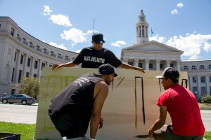 """Artist Chevy (back), Gamma (right), and one who wished not to be named begin work on a """"Black Lives Matter"""" painting at the Civic Center Park occupation on July 9, 2016. (Kevin J. Beaty/Denverite)  black lives matter; civic center park; occupy; kevinjbeaty; denver; denverite; colorado; protest;"""