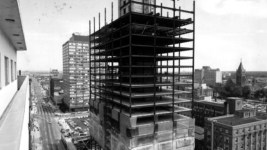 Rooftop view of the partially constructed Colorado State Savings Bank Building at 16th (Sixteenth) Street and Broadway in downtown Denver, Colorado. Automobiles and trucks drive near the skyscraper. A crane is at the construction site. July 28, 1970. (Denver Public Library/Western History Collection/X-24940)  construction; development; colorado state savings bank; denver public library; dpl; archival; archive; historic; denver; colorado; denverite;