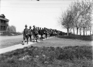 A long line of troops, some in uniform, others in civilian clothes, march along a walkway next to the barracks, Fort Logan, Colorado, a World War I assembly point for young soldiers. Some carry Army musette bags. 1917 or 1918. (George L. Beam/Denver Public Library/Western History Collection/GB-7571)  denver public library; dpl; archive; archival; world war I; military; george l beam; denverite;