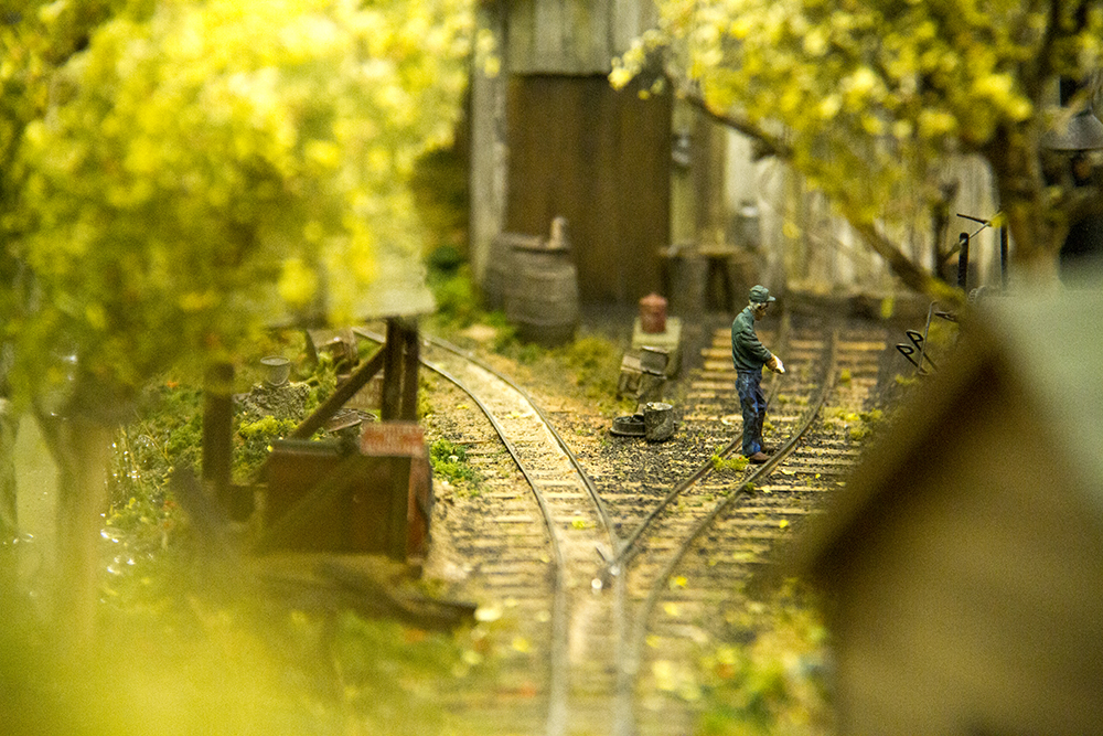 A tiny man stands on a model train track at Caboose Hobby on South Broadway. (Kevin J. Beaty/Denverite)  train; caboose hobby; model; denver; south broadway; colorado; kevinjbeaty; denverite;