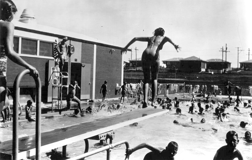 Boys and girls play at this YMCA swimming pool in Littleton, Colorado. A girl leaps from a diving board in the foreground, and a lifeguard stands atop an elevated chair. A clock and a United States flag are on the brick wall behind him, and houses are in the background. Circa 1961. (Denver Public Library/Western History Collection/X-12075)  summer; pool; historic; denver public library; dpl; archive; archival; denverite