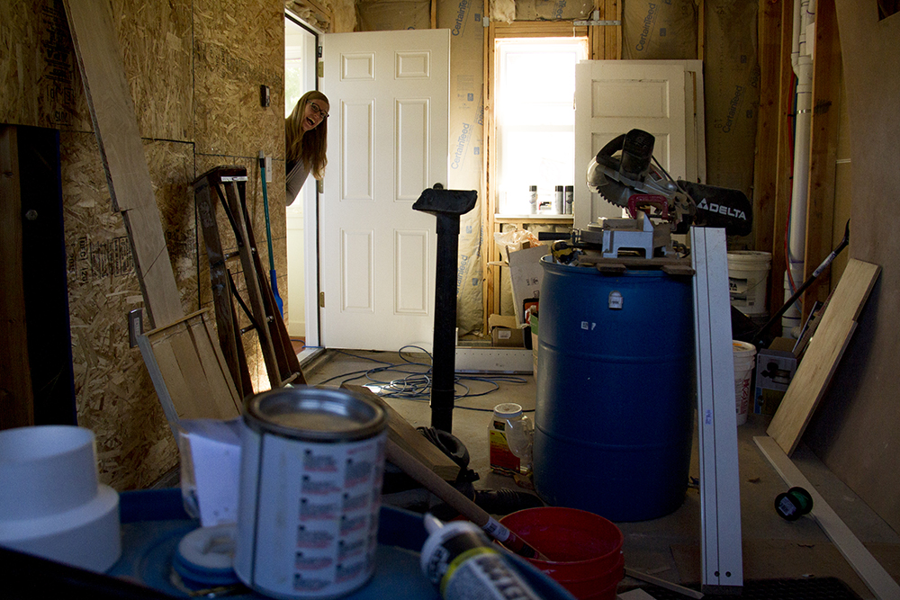 "Mara Owens pops her head into an unfinished garage beneath the ""granny flat"" or accessory dwelling unit she built with her partner Andrew Gehauf behind their home in Overland. (Kevin J. Beaty/Denverite)  residential; real estate; construction; adu; kevinjbeaty; denver; denverite; colorado; home; house; granny flat"