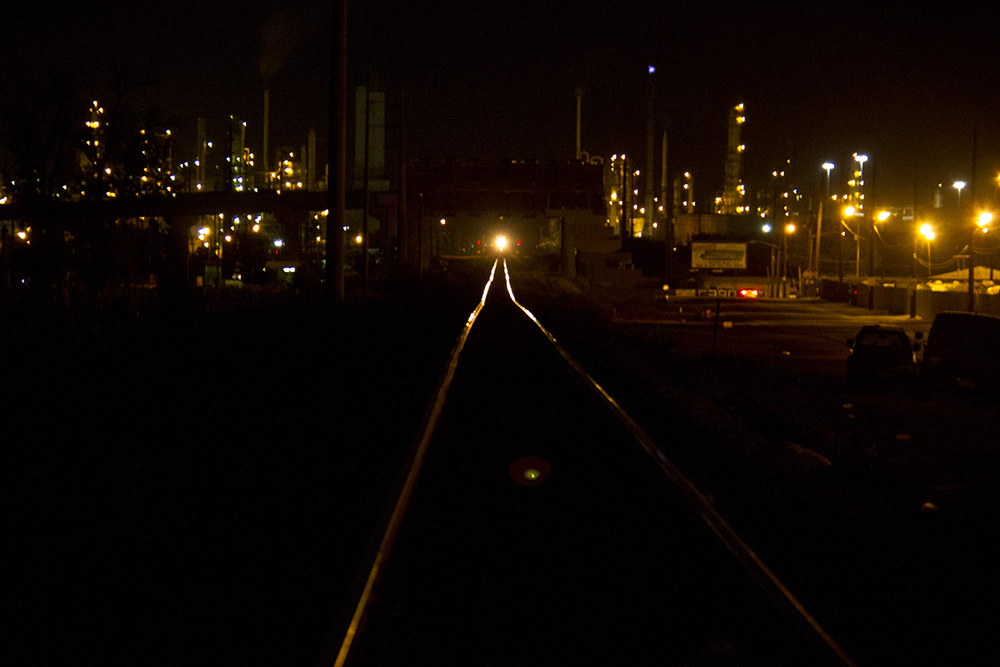A train is seen down the tracks by the Suncor refinery. (Kevin J. Beaty/Denverite)  riverside cemetery; history; kevinjbeaty; denverite; denver; colorado;