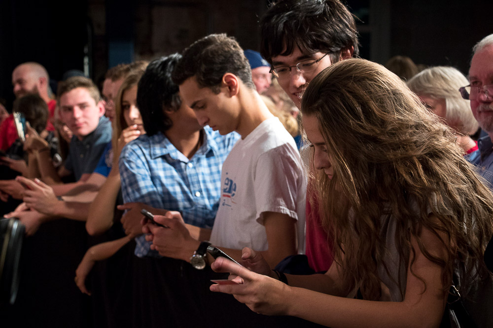 Emma Khorunshy, Avi Swartz, David Camhi, and Sid Mane, all high school student from Cherry Creek, check their phones between speakers during the Hillary Clinton rally. (Chloe Aiello/Denverite)