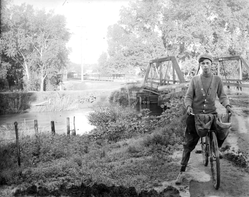 A paperboy poses on his bicycle near the Alameda Avenue bridge over Archer Canal in Denver, Colorado. The bridge over the South Platte River is in the distance. (Charles Lillybridge/History Colorado/90.152.1610 DPLY)  history colorado; historic; denver public library; dpl; archive; archival; denverite