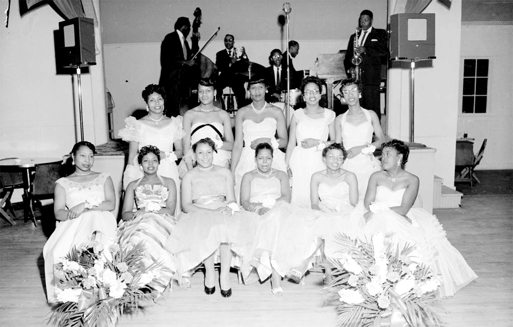 View of an Altruistic Club function. A group of African American women wear white formal dresses and pose in front of a stage in Denver, Colorado. The women may be attending a party or dance at the Disabled American Veterans hall. Members of a jazz band are in the distance. Circa 1955. (Burnis McCloud/Denver Public Library/Western History Collection/MCD-94)  five points; historic; denver public library; dpl; archive; archival; denverite