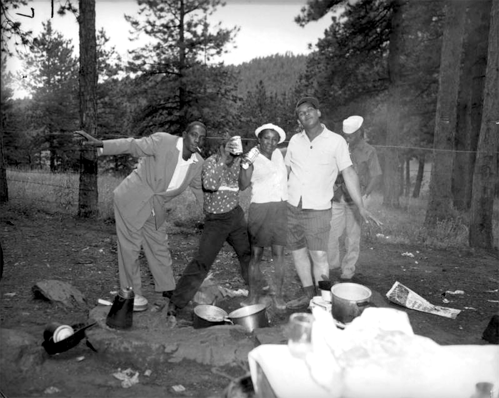A group of African American men and women, members of the Kings and Queens Social Club, pretend to be drunk at a park in the mountains near Denver, Colorado. They drape their arms around each other and stand in awkward poses. Two of the people hold Budweiser beer cans in their hands, and one man dangles a cigarette from his mouth. The ground is littered with pots, pans, a coffee pot, and papers. Between 1955 and 1965. (Burnis McCloud/Denver Public Library/Western History Collection/MCD-183)  five points; historic; denver public library; dpl; archive; archival; denverite