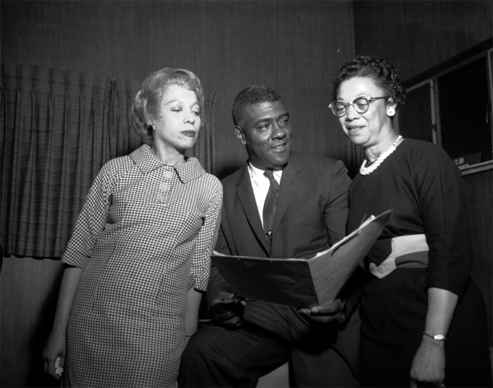 """Two African American women and a man look at a file in a paneled room in Denver, Colorado. The women wear dresses with three quarter length sleeves. The man wears a suit and tie. A sign reading: """"Owl Club"""" leans on a window in the distance. Between 1955 and 1965. (Burnis McCloud/Denver Public Library/Western History Collection/MCD-218)  five points; historic; denver public library; dpl; archive; archival; denverite"""
