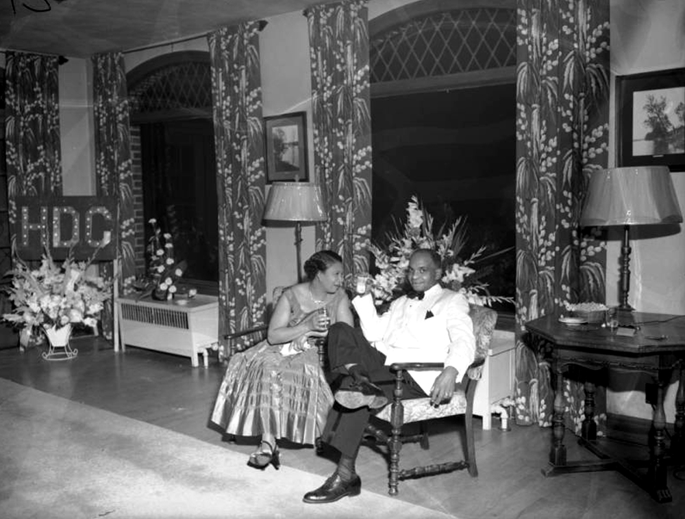 An African American (Black) couple sit in chairs in a large opulent room in an unknown location in Denver, Colorado. The woman wears a party dress and speaks to a man dressed in a tuxedo, they both hold drinks. A sign in the distance reads H.D.C., identified as a social club. Between 1950 and 1960. (Burnis McCloud/Denver Public Library/Western History Collection/MCD-165)  five points; historic; denver public library; dpl; archive; archival; denverite