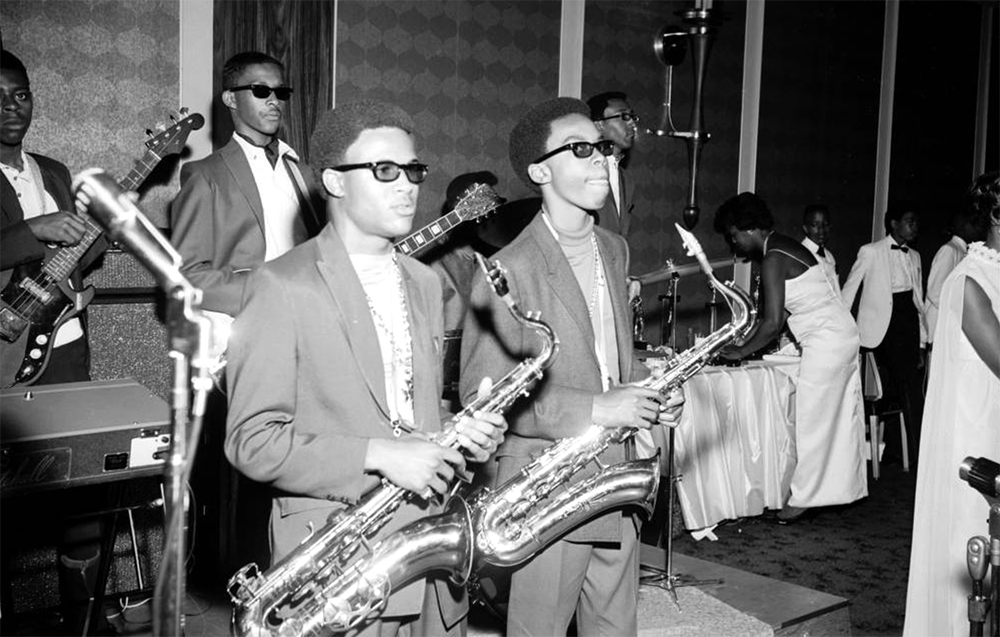 Members of a teenage jazz band stand on a stage at a dance in Denver, Colorado. Some of the African American (Black) musicians have their hair styled in short Afros and wear thick framed black glasses. The saxophone players wear turtlenecks, suit jackets, and thick gold chains. Shows saxophones, base guitar, lead guitar, and drums. Women in white full length formal dresses and men in tuxedos are in the distance. (Burnis McCloud/Denver Public Library/Western History Collection/MCD-134)  five points; historic; denver public library; dpl; archive; archival; denverite