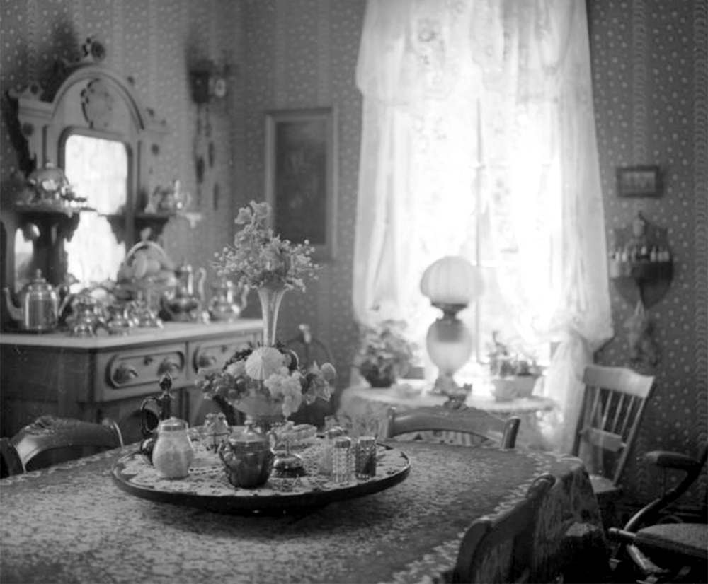 Daylight streams through the lace curtains of a dining room in Central City, Colorado. Between 1960 and 1980. (Sandra Dallas/Denver Public Library/Western History Collection/X-2882)  history colorado; historic; denver public library; dpl; archive; archival; denverite