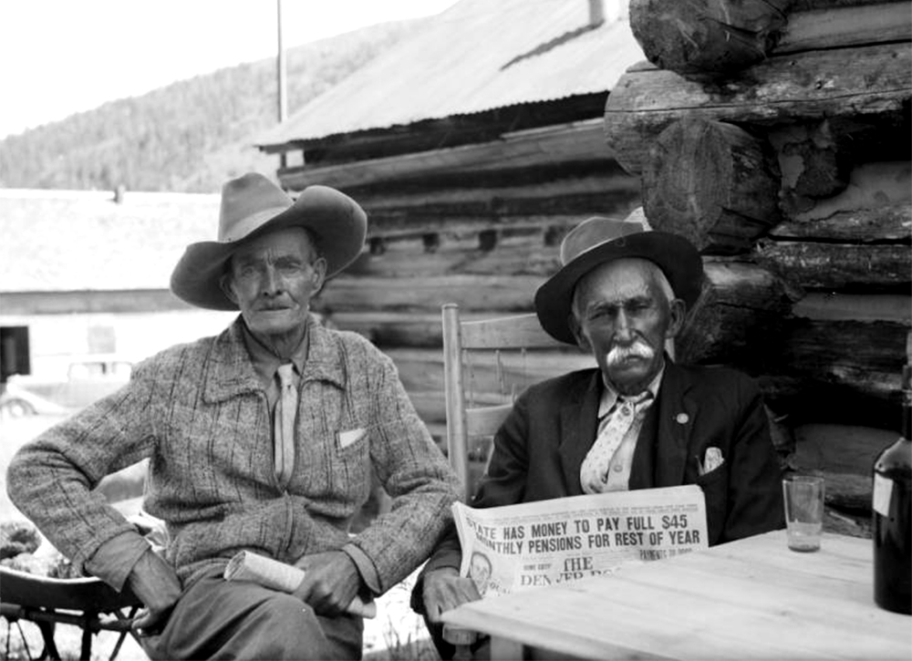 SummaryJ. B. Rowley, left, and John A. Gilfillan, right, sit at a table in front of a log cabin, probably in Eldora, a mining town in Boulder County, Colorado. The two men were pioneers of the town in the 1890s. Rowley was a prospector and a small mine operator in Boulder County. Gilfillan was a mining engineer who staked a claim on the Clara Lode on Spencer Mountain in 1889. Circa 1939. (Donald Kemp/Denver Public Library/Western History Collection/K-302)  five points; historic; denver public library; dpl; archive; archival; denverite