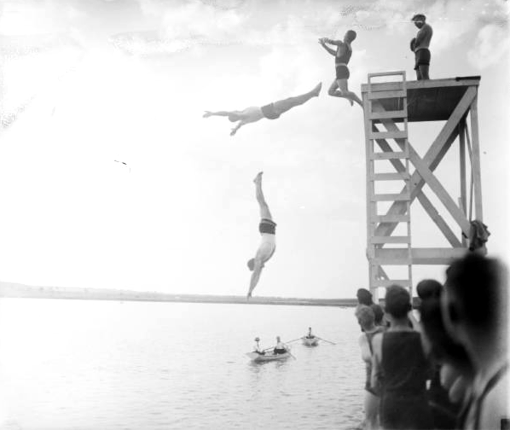Men or teenaged boys in swimming suits dive from a tower by a lake; men in row boats look on. Between 1910 and 1930. (Harry Mellon Rhoads/Denver Public Library/Western History Collection/Rh-2022)  historic; denver public library; dpl; archive; archival; denverite