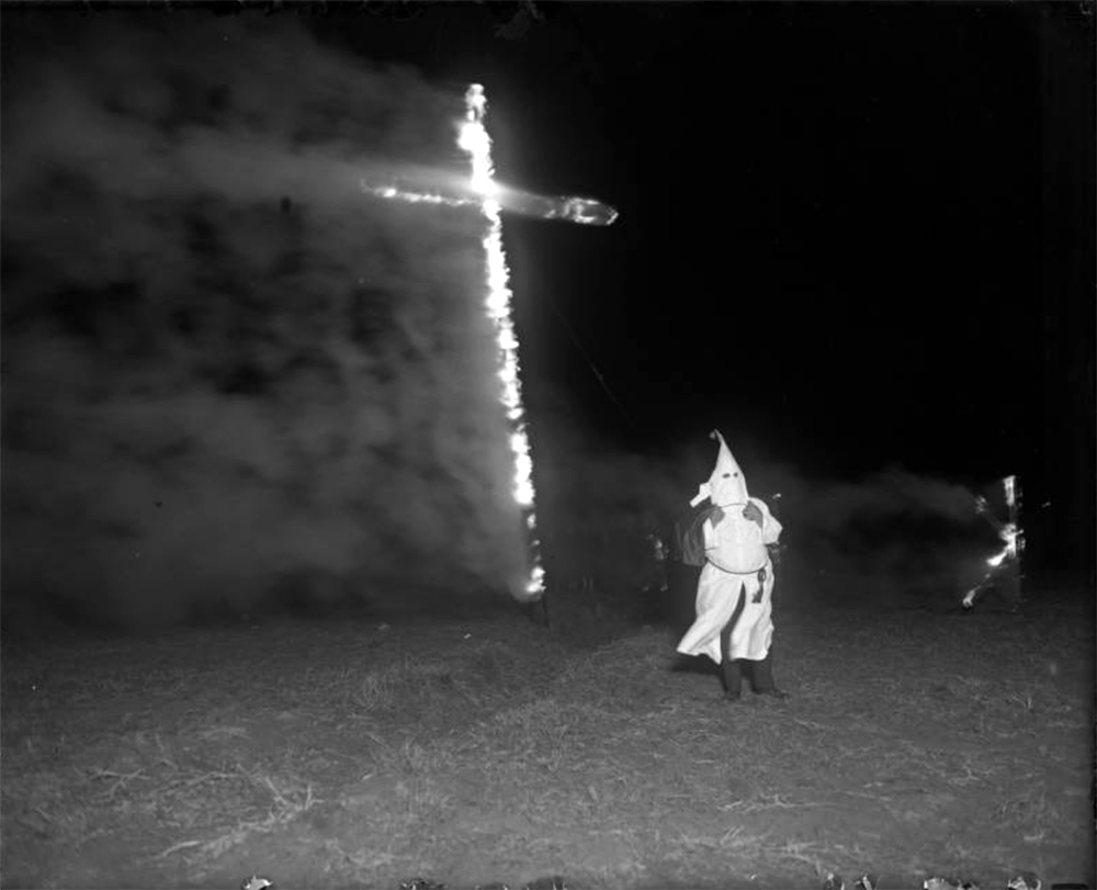 View of a burning cross on Ruby Hill, in Denver, Colorado; a man in Ku Klux Klan uniform and hood is to the side. Between 1920 and 1930. (Harry Mellon Rhoads/Denver Public Library/Western History Collection/Rh-595)  historic; denver public library; dpl; archive; archival; denverite